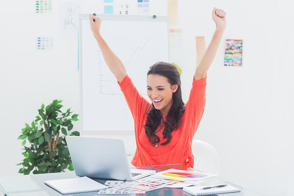 Excited woman raising her arms while working on her laptop in her office-1