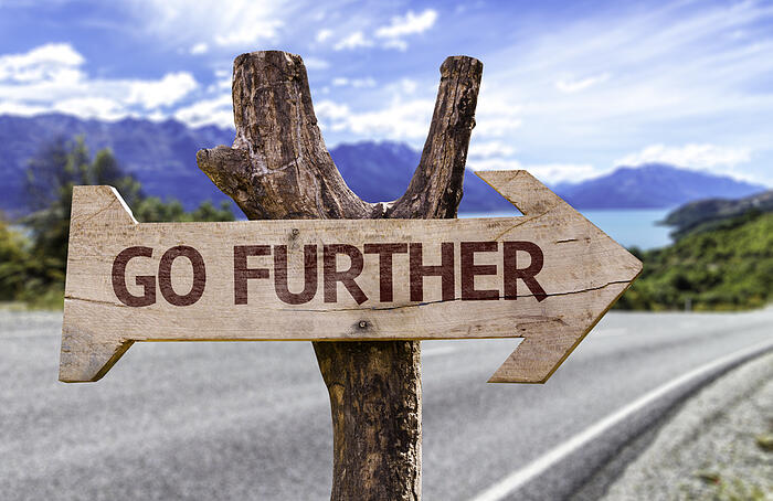 Go Further wooden sign with a paradise on background